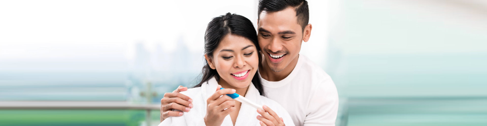 happy couple looking at a positive pregnancy test result
